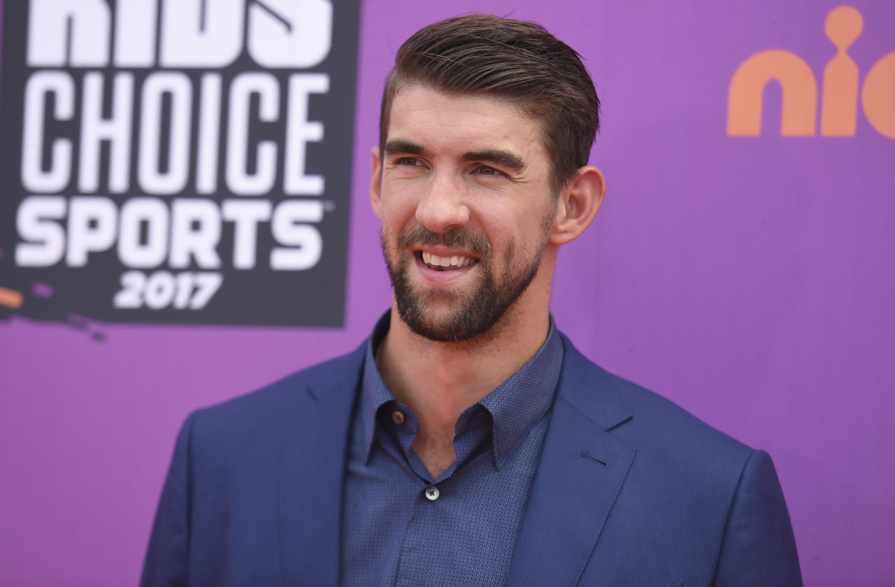 "FILE - In this July 13, 2017 file photo, retired Olympic swimmer Michael Phelps arrives at the Kids' Choice Sports Awards at UCLA's Pauley Pavilion in Los Angeles. Discovery Channel's Shark Week's opening lineup Sunday, July 23, includes ""Phelps vs. Shark: Great Gold vs. Great White,"" with Phelps testing his speed against that of a great white shark. (Photo by Richard Shotwell/Invision/AP, File)"