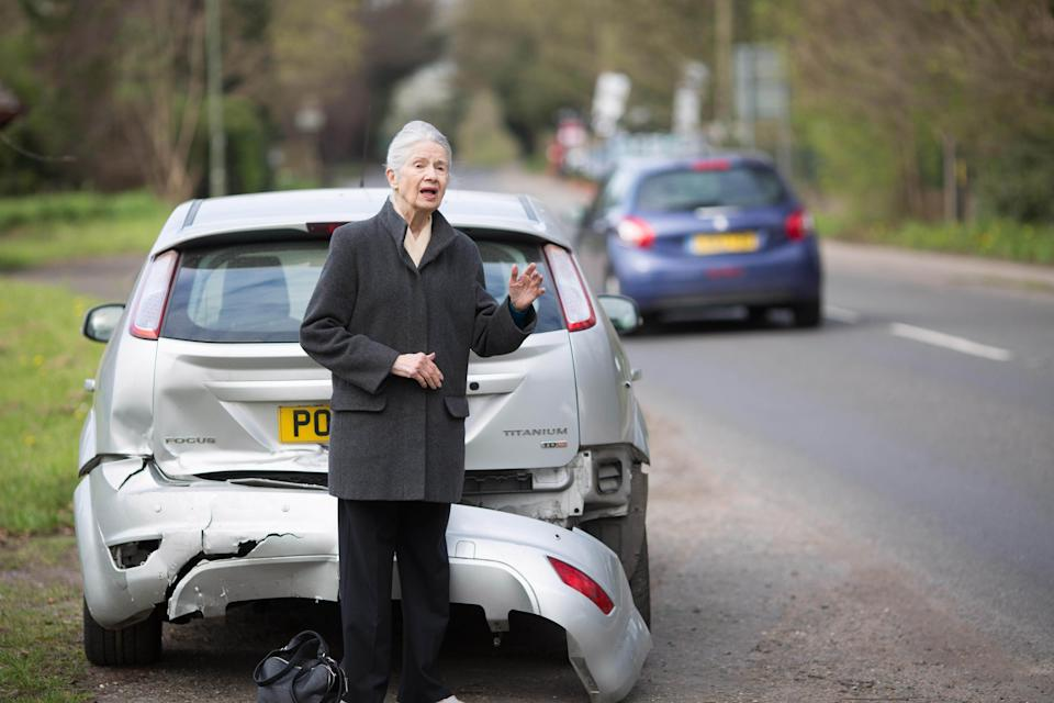 A woman waiting beside a damaged car (PA Archive)
