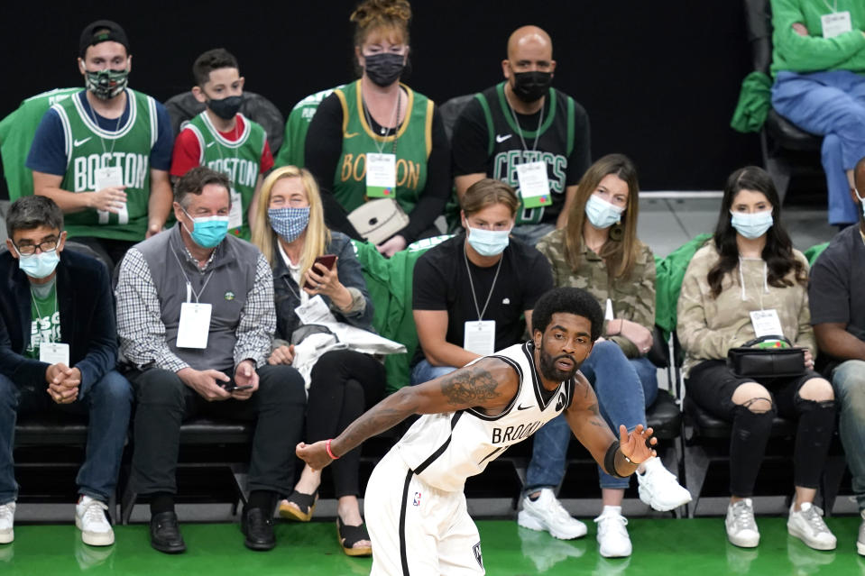 Fans watch as Brooklyn Nets guard Kyrie Irving runs up the court during the second quarter of Game 3 against the Boston Celtics during an NBA basketball first-round playoff series Friday, May 28, 2021, in Boston. Irving was repeatedly booed by spectators. (AP Photo/Elise Amendola)