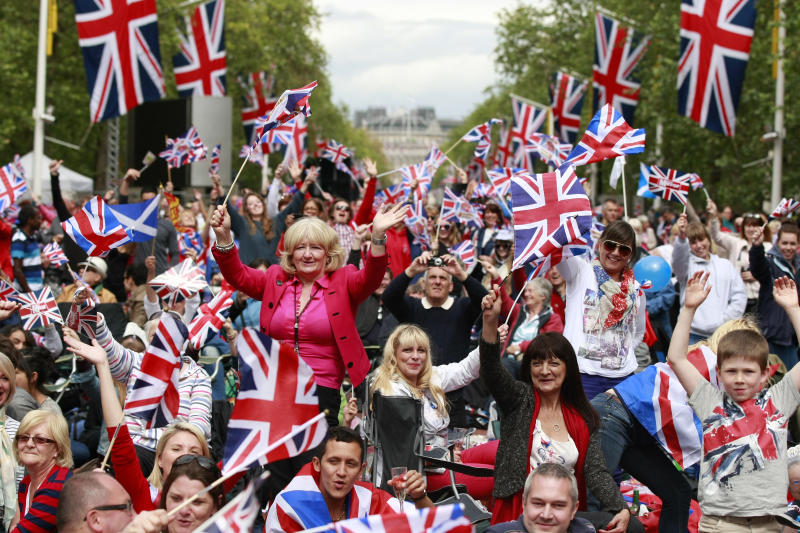 Members of the public sit on the Mall while waiting for the start of a pop music concert at Buckingham Palace to help celebrate Britain's Queen Elizabeth II's 60-year reign during Diamond Jubilee celebrations in London, Monday, June 4, 2012. (AP Photo/Tim Hales)