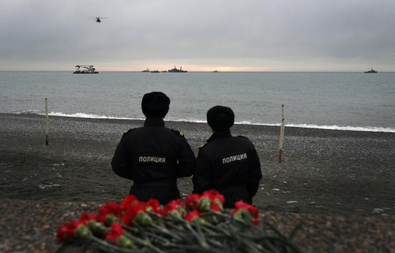 Russian police officers look at the rescue vessels searching the Black Sea outside Sochi two days after the plane crashed on its way to a Russian military airbase in Syria