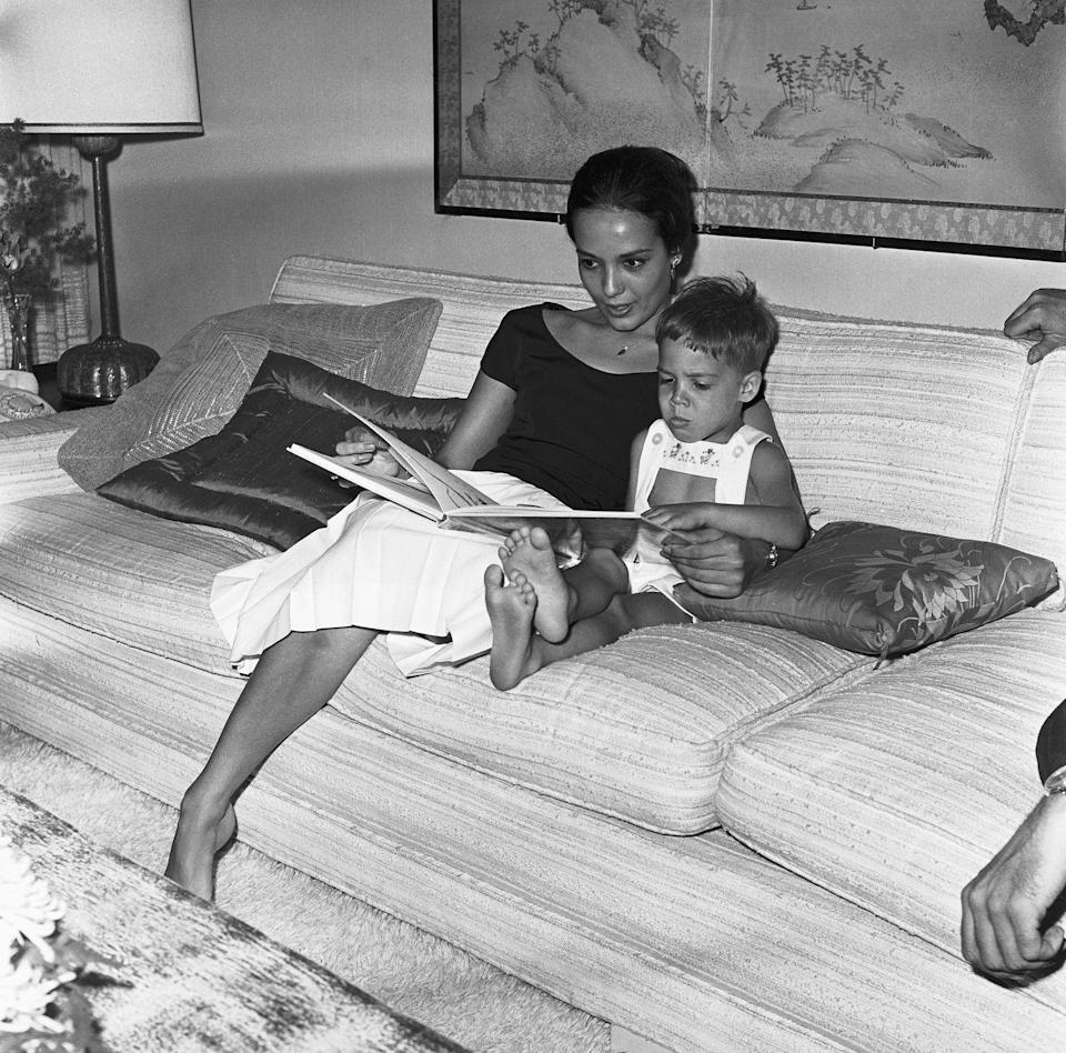 <p>Marlon Brando's ex-wife snuggles up with their son, Christian Brando, while reading him a book in 1961. </p>