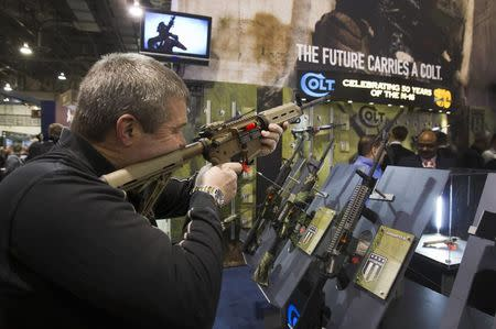 Mark Heitz, of Tactical Firearms in Kingston, New Hampshire, looks over a civilian version of the Colt M4 carbine during the annual SHOT (Shooting, Hunting, Outdoor Trade) Show in Las Vegas January 15, 2013.  REUTERS/Las Vegas Sun/Steve Marcus/File Photo