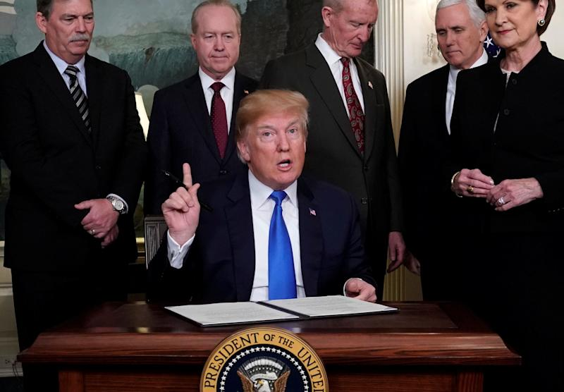 U.S. President Donald Trump, surrounded by business leaders and administration officials, prepares to sign a memorandum on intellectual property tariffs on high-tech goods from China, at the White House in Washington, U.S. March 22, 2018.  (Photo: Jonathan Ernst / Reuters)