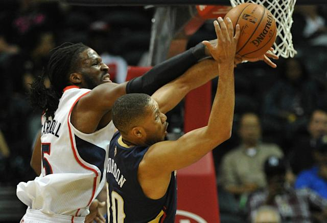 Atlanta Hawks' DeMarre Carroll, left, and New Orleans Pelicans' Eric Gordon, right, battle for the rebound in the first half of their NBA basketball game Friday, March 21, 2014, in Atlanta. (AP Photo/David Tulis)