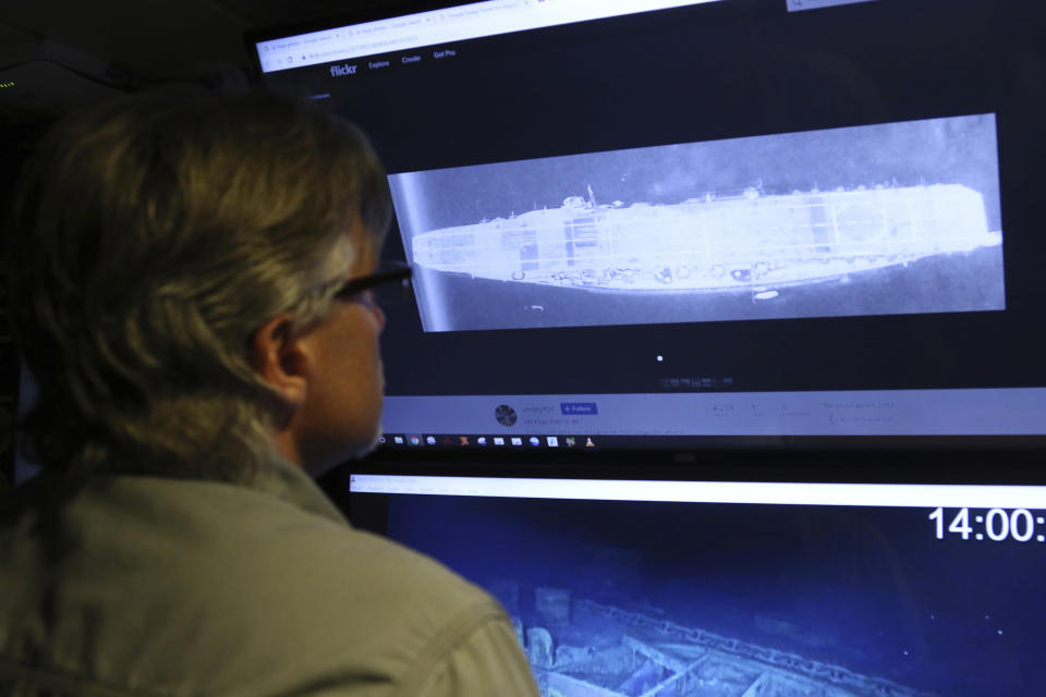 In this Wednesday, Oct. 16, 2019, photo, Vulcan Inc. director of subsea operations on the Petrel, Rob Kraft, left, looks at images of the Japanese aircraft carrier Kaga, off Midway Atoll in the Northwestern Hawaiian Islands. Deep-sea explorers scouring the world's oceans for sunken World War II ships are honing in on a debris field deep in the Pacific. Weeks of grid searches around the Northwestern Hawaiian Islands already have led the research vessel Petrel to one sunken battleship, the Japanese aircraft carrier Kaga. This week, it's investigating what could be another. (AP Photo/Caleb Jones)