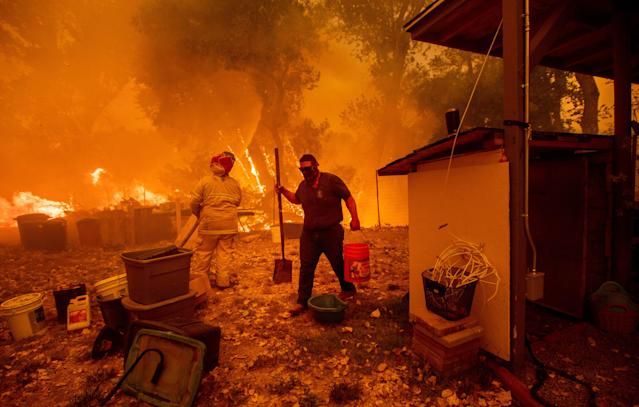 <p>Resident Lane Lawder carries a water bucket while fighting to save his home from the Ranch Fire burning down New Long Valley Rd near Clearlake Oaks, Calif., on Aug. 4, 2018. (Photo: Noah Berger/AFP/Getty Images) </p>