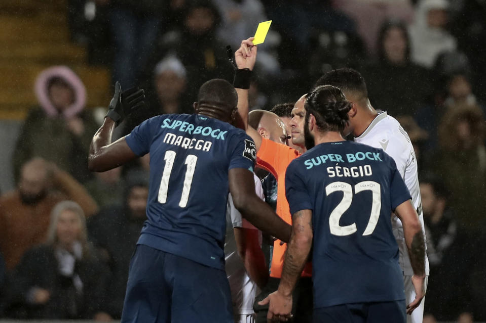 Referee Luis Godinho shows a yellow card to Porto's Moussa Marega, left, during a Portuguese league soccer match between Vitoria SC and FC Porto in Guimaraes, Portugal, Sunday, Feb. 15, 2020. The president and the prime minister of Portugal have added their voices to a national outcry over racist abuse aimed at Moussa Marega who walked off the field after hearing monkey chants. (AP Photo)