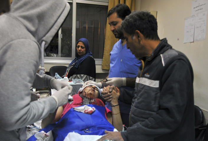 """In this photo released by the Syrian official news agency SANA, a paramedic treats an injured woman wounded by Israeli missile strikes at a hospital in Damascus, Syria, Wednesday, Nov. 20, 2019. The Israeli military on Wednesday said it struck dozens of Iranian targets in Syria, carrying out a """"wide-scale"""" strike in response to rocket fire on the Israeli-controlled Golan Heights the day before. (SANA via AP)"""
