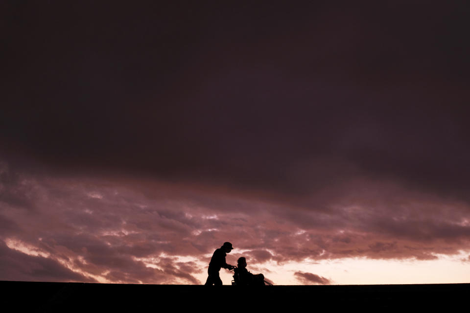 A man pushes a woman in a wheelchair as they stroll along the seawall against the sunset sky while wearing face masks to protect against the coronavirus Sunday, Nov. 22, 2020, in Shizuoka, southwest of Tokyo, Japan. (AP Photo/Kiichiro Sato)