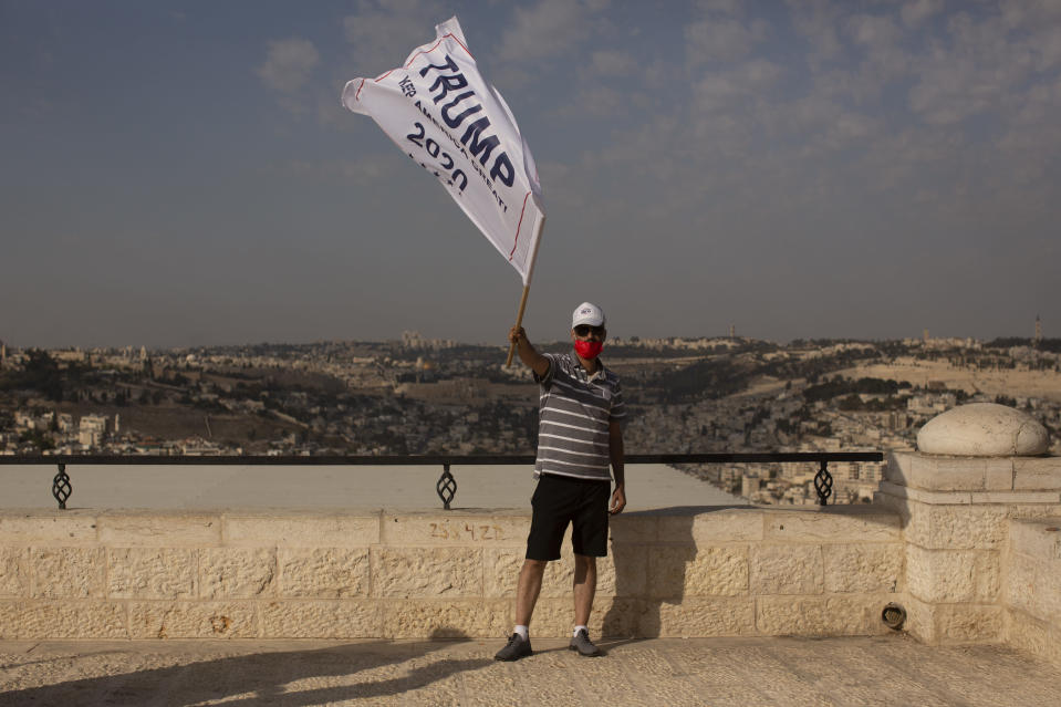 An Israeli supporter of U.S. President Donald Trump waves a campaign flag at a rally for his re-election, on a promenade overlooking Jerusalem, Tuesday, Oct. 27, 2020. (AP Photo/Maya Alleruzzo)