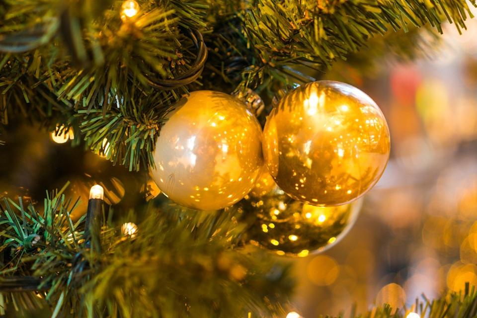 An ornament cluster of gold ornaments hanging on a Christmas tree