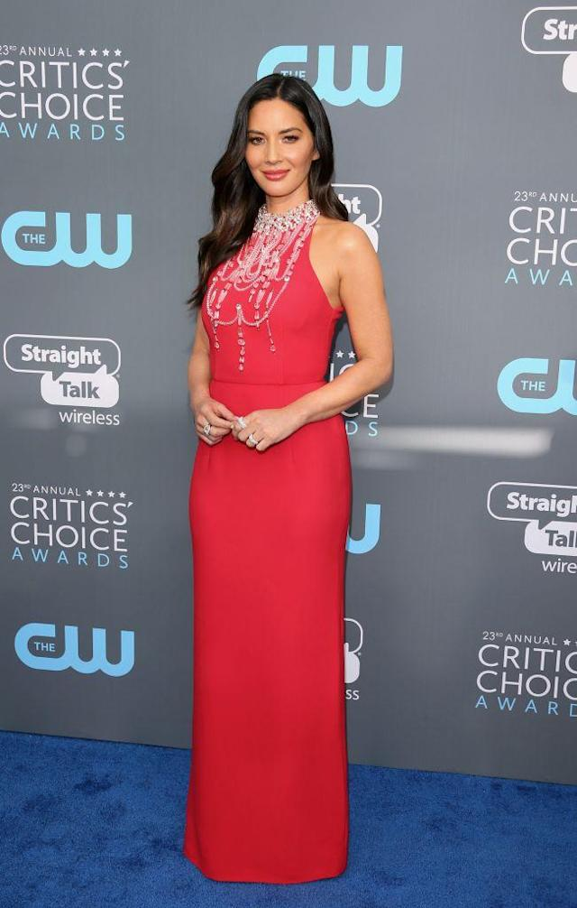 The host arrived on the blue carpet in a red dress with glitzy details. (Photo: Getty Images)