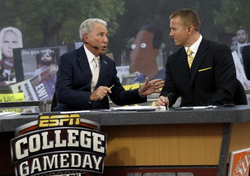 ESPN College GameDay hosts Lee Corso, left, and Kirk Herbstreit confer during the telecast from The Junction prior to Mississippi State playing Auburn in an NCAA college football game in Starkville, Miss., Saturday, Oct 11, 2014. No.3 Mississippi State beat No. 2 Auburn 38-23. (AP Photo/Rogelio V. Solis)