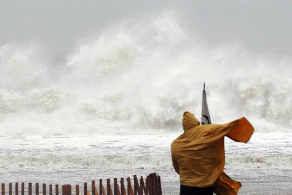 A Rehoboth Beach resident watches waves crash down in Delaware, Monday, Oct. 29, 2012. Hurricane Sandy continued on its path Monday, forcing the shutdown of mass transit, schools and financial markets, sending coastal residents fleeing for higher ground, and threatening a dangerous mix of high winds and soaking rain. (AP Photo/The Wilmington News-Journal, Suchat Pederson) NO SALES