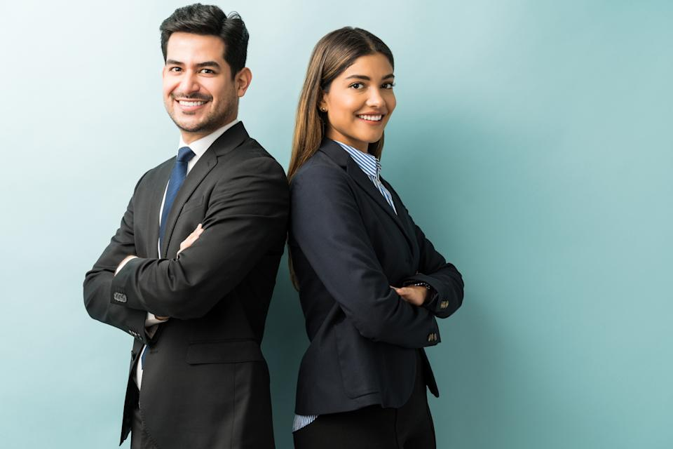 Confident professionals in suit standing against isolated background