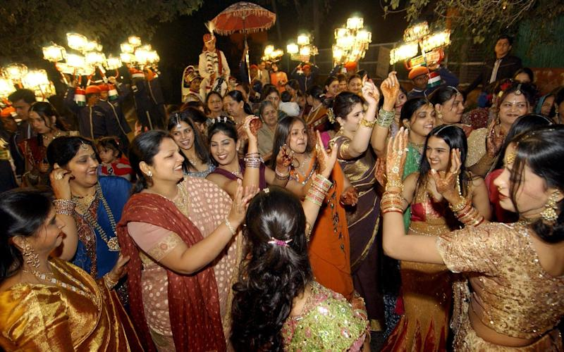 An Indian Hindu wedding party dances upon the arrival of the bridegroom - AFP