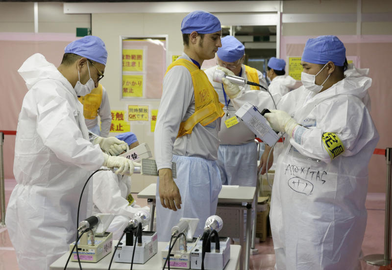Tokyo Electric Power Co. workers check the level of radioactivity on a foreign journalist after he visited the tsunami-crippled Fukushima Daiichi Nuclear Power Plant, in Okuma, Fukushima Prefecture, northeast of Tokyo, on July 9, 2014