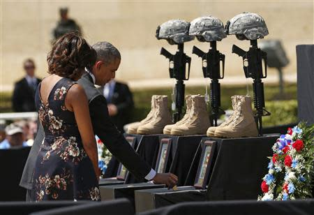 U.S. President Barack Obama places a challenge coin on a memorial as he and first lady Michelle Obama pay their respects for the dead soldiers at the conclusion of service in Fort Hood