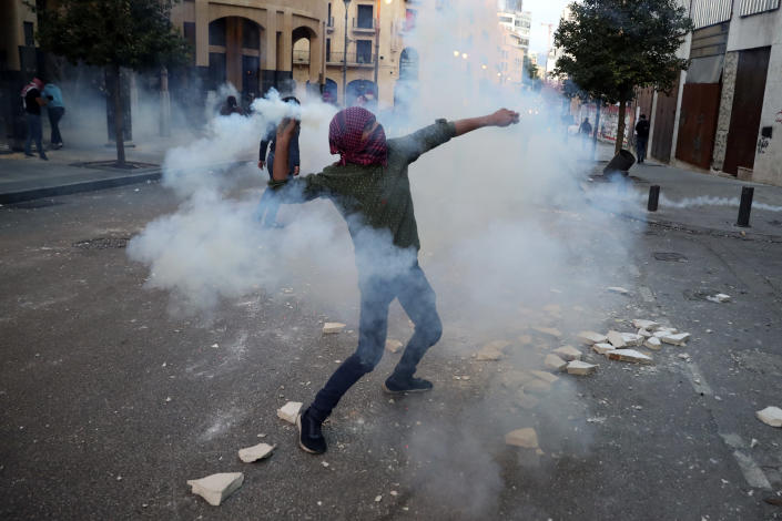 A protester throws back a tear gas canister towards riot policemen, during a protest near Parliament Square, In Beirut, Lebanon, Saturday, March. 13, 2021. Riot police fired tear gas to disperse scores of people who protested near parliament building in central Beirut Saturday amid deteriorating economic and financial conditions and as the local currency hit new low levels. (AP Photo/Bilal Hussein)
