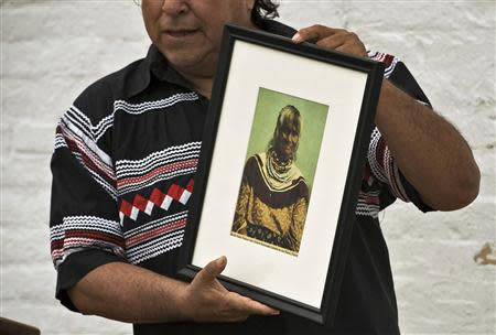 "Seminole Tribe member and historian Willie Johns holds up a photograph of Polly Parker during a visit to Egmont Key State Park as part of a historic journey to retrace the ""Voyage of Tears"" in Egmont Key, Florida, December 1, 2013. REUTERS/Steve Nesius"