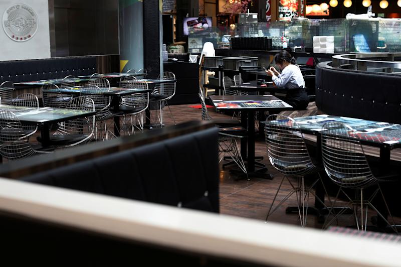 A woman dines in an empty restaurant, during the coronavirus disease (COVID-19) outbreak, in Singapore, August 12, 2020. REUTERS/Edgar Su