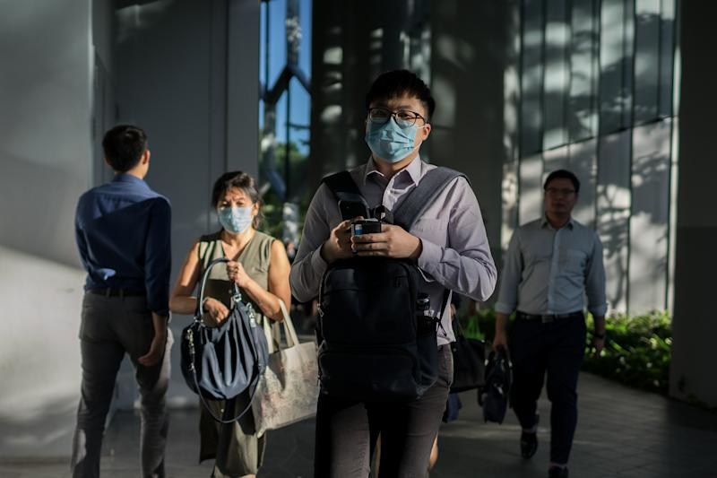 SINGAPORE - 2020/02/17: Office workers wearing protective face masks after working hours following the corona virus threat. Singapore declared the COVID-19 outbreak as Code Orange on February 7, 2020. (Photo by Maverick Asio/SOPA Images/LightRocket via Getty Images)