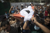 Mourners carry the body of Palestinian Omar al-Nile, 12, who was shot on Saturday during a violent demonstration on the eastern border between Gaza and Israel, during his funeral in Gaza City, Saturday, Aug. 28, 2021. (AP Photo/Khalil Hamra)