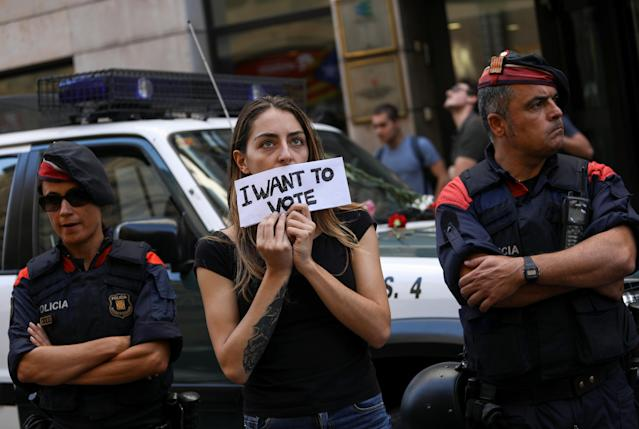 <p>A protestor holds up a sign in front of a Catalan police outside the Catalan region's foreign affairs ministry building during a raid by Spanish police on government offices, in Barcelona, Spain, Sept. 20, 2017. (Photo: Susana Vera/Reuters) </p>
