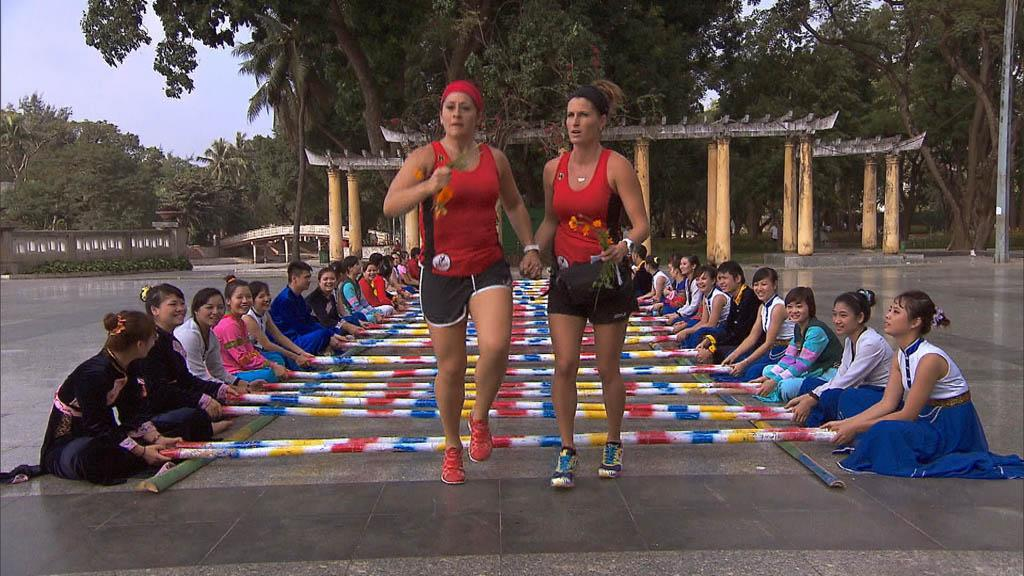 """Your Tan is Totally Cool"" -- At the Detour Decision Point, Roller Derby moms Beth (left) and Mona (right) must perform the Mua Sapa, the Vietnamese bamboo dance, in order to receive the next clue on ""The Amazing Race."""