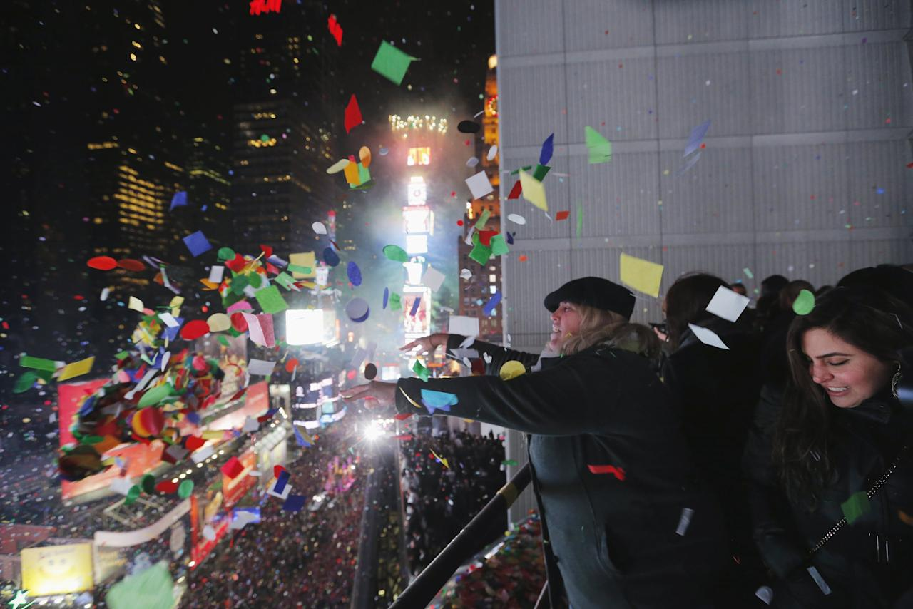Revelers throw confetti from a balcony to celebrate during New Year festivities above Times Square in New York January 1, 2016. REUTERS/Lucas Jackson