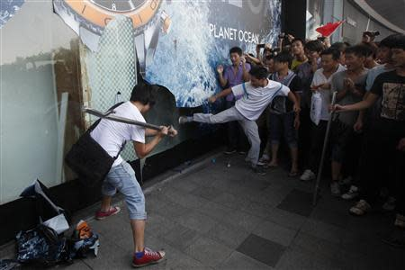 Demonstrators damage the windows of a Japanese Seibu department store during a protest against Japan's decision to purchase disputed islands, which Japan calls the Senkaku and China calls the Diaoyu, in Shenzhen, south China's Guangdong province in this September 16, 2012 file photo. REUTERS/Tyrone Siu/Files