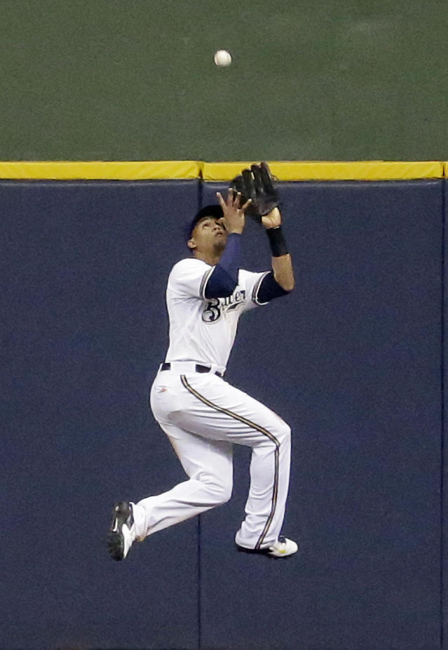 Milwaukee Brewers center fielder Carlos Gomez leaps and catches a ball hit by Minnesota Twins' Trevor Plouffe during the eighth inning of a baseball game, Monday, June 2, 2014, in Milwaukee. (AP Photo/Morry Gash)