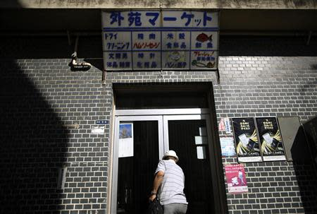 Resident Kohei Jinno, 79, closes the door of his shop at Kasumigaoka apartment complex which is located near the National Olympic Stadium in Tokyo September 18, 2013. REUTERS/Issei Kato
