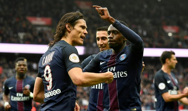 Paris Saint-Germain's Edinson Cavani (L) is congratulated by teammates after scoring a goal during their French L1 football match against Montpellier at the Parc des Princes stadium in Paris on April 22, 2017