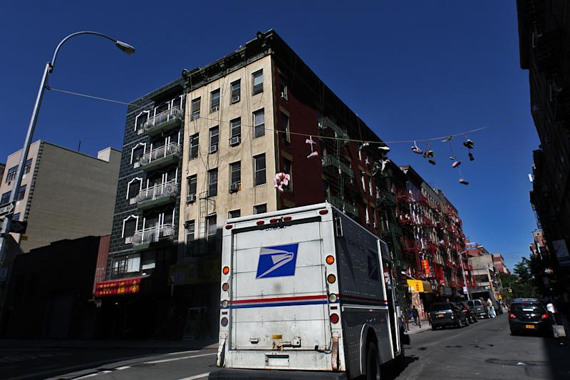 A United States Postal Services mail truck driving past orchard street in the Chinatown neighborhood in Manhattan, New York City.