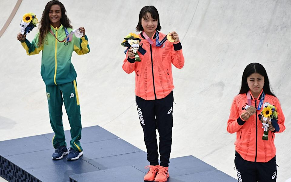 Japan's Momiji Nishiya (13) shows off her gold in the central, with Brazil's Rayssa Leal (13) and Funa Nakayama (16) either side - AFP