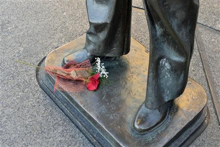 A lone bouquet of flowers is left at the base of a statue at the Navy Memorial in Washington, to honor the victims of the attack at the Navy Yard