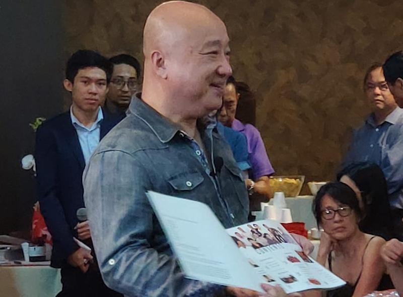 SDP media management head Benjamin Pwee showing the coffee-table book 'The Way Forward' on 28 September, 2019. (PHOTO: SDP)