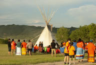 A vigil takes place where ground-penetrating radar recorded hits of what are believed to be 751 unmarked graves near the grounds of the former Marieval Indian Residential School on the Cowessess First Nation, Saskatchewan, Saturday, June 26, 2021. (Mark Taylor/The Canadian Press via AP)