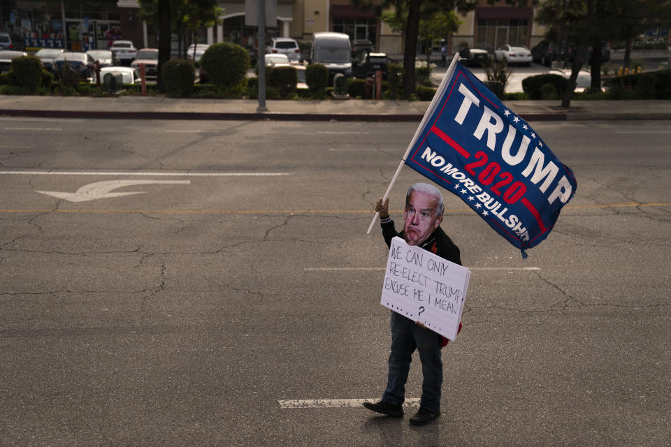 """Wearing a paper mask to mock Democratic presidential candidate former Vice President Joe Biden, Gabriel Lebaron, 35, attends a rally held in support of President Donald Trump in the Tujunga section of Los Angeles, Friday, Oct. 23, 2020. """"Trump cares about America. He is an American who cares about America.'"""" said Lebaron. """"Being a Trump supporter in California is hard. I probably had three guns pulled on me in the last six months."""" (AP Photo/Jae C. Hong)"""
