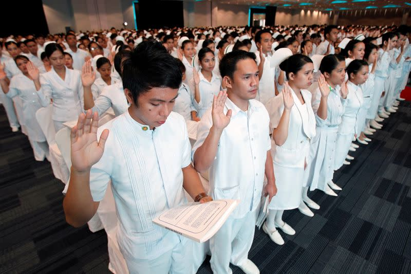 FILE PHOTO: Newly graduate nurses take their oath during an oath taking ceremony of professional nurses inside a mall in Manila