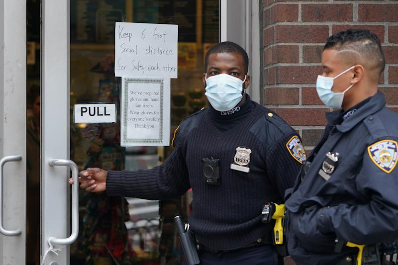 "Officials walk into a store that has a ""Social Distancing"" sign on the door during the outbreak of coronavirus disease (COVID-19), in the Manhattan borough of New York City"