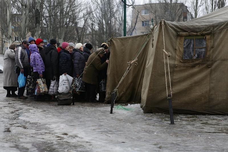 Residents of the war-scarred and cashed-starved Ukraine queue outside a tent to get warm clothes in Avdiivka, Donetsk region, on February 5, 2017 (AFP Photo/Aleksey FILIPPOV)