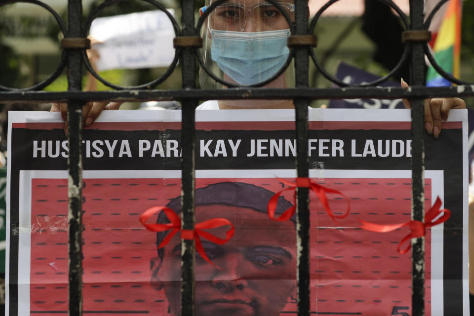 A protester holds a slogan with a picture U.S. Marine Lance Cpl. Joseph Scott Pemberton during a rally outside the Department of Justice in Manila, Philippines on Thursday Sept. 3, 2020. A Philippine court has ordered the early release for good conduct of Pemberton who was convicted in the 2014 killing of transgender Filipino Jennifer Laude which sparked anger in the former American colony. (AP Photo/Aaron Favila)