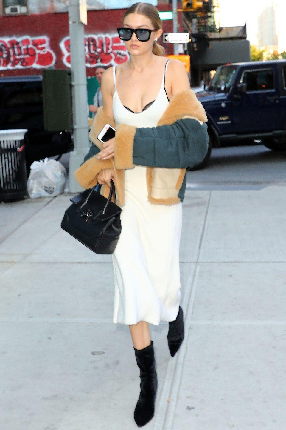 <p>In a Victoria Beckham midi slip dress with a draped shearling coat and the perfect black accessories—oversized shades, velvety booties and a Versace handbag.</p>