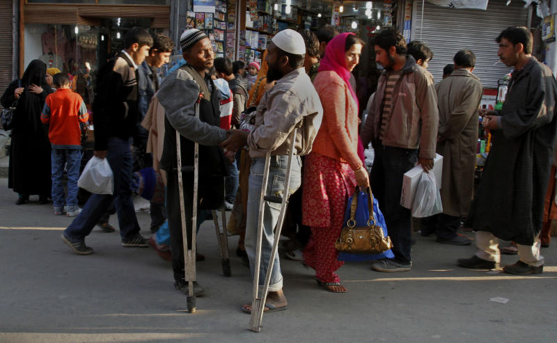 Two physically disabled under privileged men greet each other Kashmiri Muslims shop ahead of the Eid al-Adha festival, in Srinagar, India, Sunday, Nov.14, 2010. Muslims will celebrate Eid al-Adha on Nov.17 by slaughtering animals to commemorate God's gift of a ram to substitute for Abraham's impending sacrifice of his son and is considered the most important holiday in the Islamic calendar.(AP Photo/Mukhtar Khan