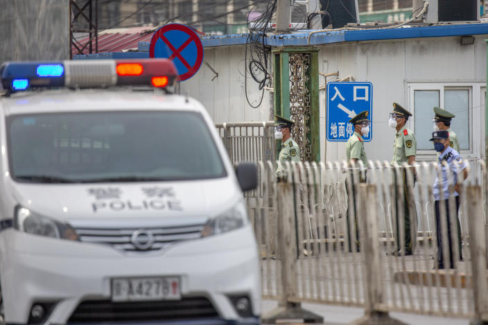 Paramilitary police stand guard on a street near the Xinfadi wholesale food market district in Beijing, Saturday, June 13, 2020. Beijing closed the city's largest wholesale food market Saturday after the discovery of seven cases of the new coronavirus in the previous two days. (AP Photo/Mark Schiefelbein)