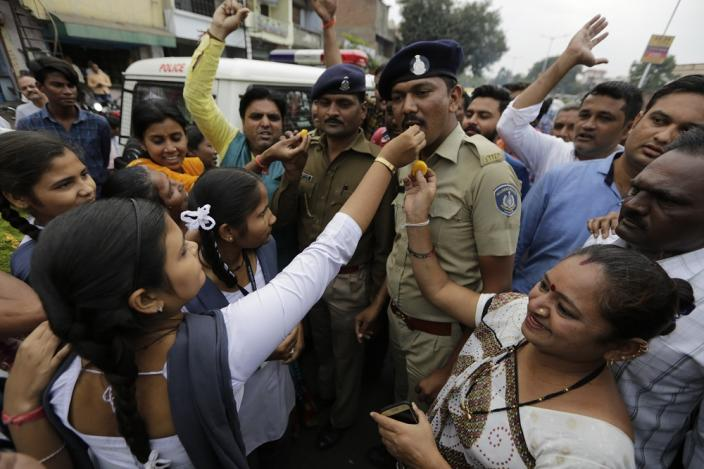 Indian women feed sweets to policemen on duty and shout slogans to celebrate the killing of four men suspected of raping and killing a woman in Telangana, in Ahmadabad, on Friday, December 6, 2019. (AP Photo/Ajit Solanki)