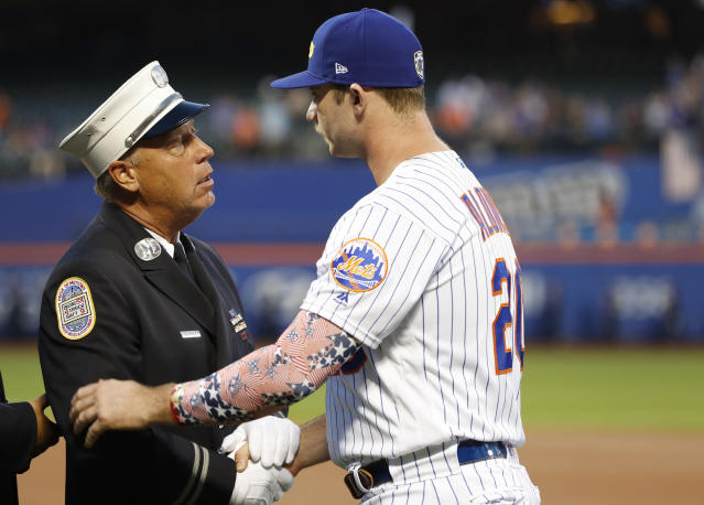 A member of the New York City Fire Department greets New York Mets' Pete Alonso during a Sept. 11, 2001, tribute before the team's baseball game against the Arizona Diamondbacks on Wednesday, Sept. 11, 2019, in New York. (AP Photo/Kathy Willens)